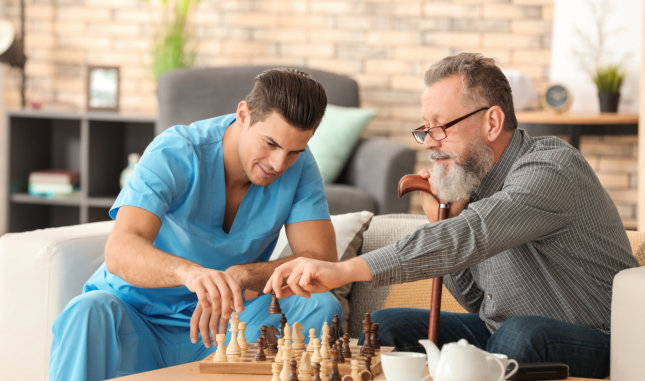 caretaker playing chess with a senior man