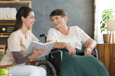female care with senior woman on wheelchair smiling at each other