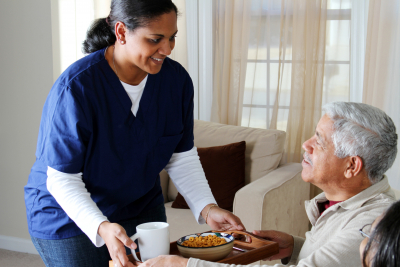 female caregiver serving snacks to senior woman