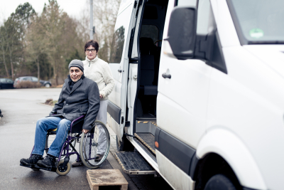 woman with senior man on wheelchair exiting in van