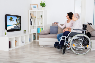 senior woman with female caregiver watching tv